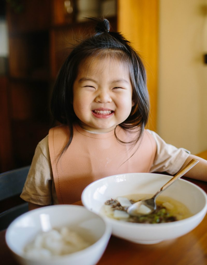 Happy toddler eating Korean Beef Radish Soup